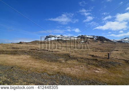 Beautiful Rugged Snow Covered Mountains And Farms In Iceland.