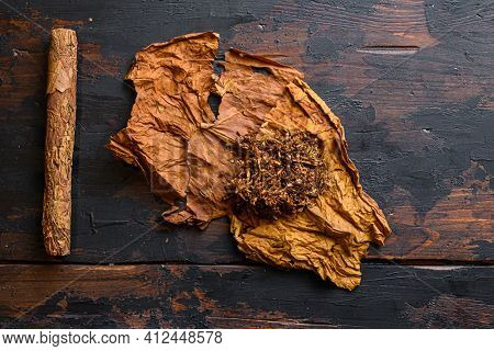 Cut Tobacco And Tobacco Leaves With Cigar On Background On Vintage Dark Table. Overhead Shot Top Vie