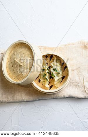 Bamboo Steamer Of Japanese Gyoza, Dumplings Snack , On Linen Cloth Served On White Textured Stone Ta