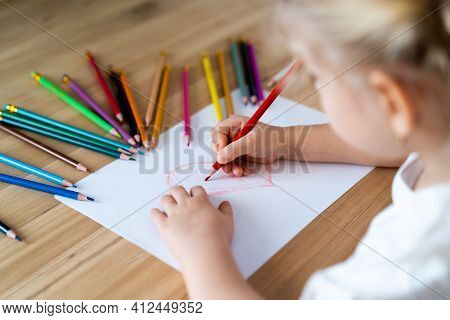 A Little Blonde Girl Is Sitting At The Table, Smiling And Drawing A Heart With A Red Pencil, There A