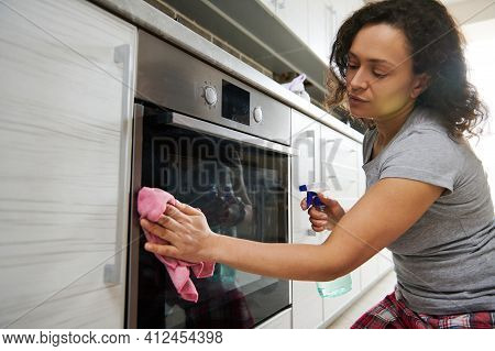 Woman Cleaning The Surface Of An Electric Stove. Home Work And Cleaning Concept
