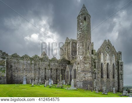 Graveyard With Celtic Crosses And Tombstones In Front Of Majestic Rock Of Cashel Castle, County Tipp