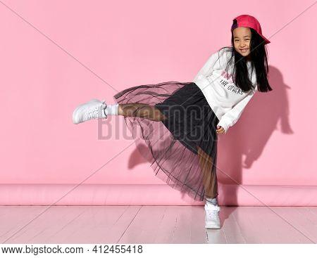 Side View Of Fashion Portrait Of Little Korean Girl Model Posing In Studio Against Pink Background,