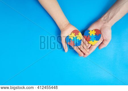Father And Autistic Son Hands Holding Jigsaw Puzzle Heart Shape. Autism Spectrum Disorder Family Sup