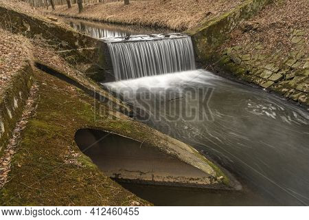 Dobrovodsky Creek With Cascade And Concrete Pipe In Cold Winter Day