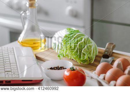 Online Cooking. Preparing Salad Using Digital Cookbook. Fresh Vegetables And Laptop In Home Kitchen.