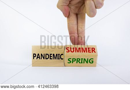 Pandemic Spring And Summer Symbol. Businessman Turns Wooden Cubes And Changes Words 'pandemic Spring