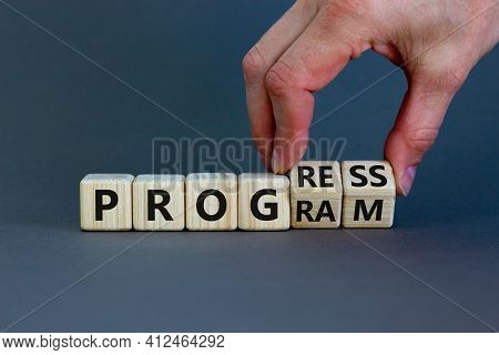 Progress And Program Symbol. Businessman Turns Wooden Cubes And Changes The Word 'program' To 'progr