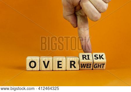 High Risk From Overweight Symbol. Doctor Turns Wooden Cubes And Changes The Words Overweight To Over