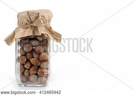 Hazelnuts In Glass Jar On A White Background. Isolated. Dried Nuts. Hazelnuts In Glass Jar Isolated