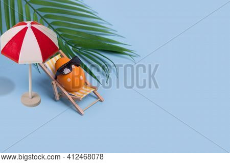 Creative Funny Composition With Easter Egg With Sunglasses Sitting On Deck Chair And Sun Umbrella On
