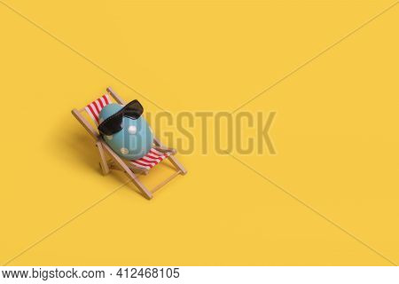 Creative Funny Idea With Easter Egg With Sunglasses While Sitting On Deck Chair On Illuminating Yell