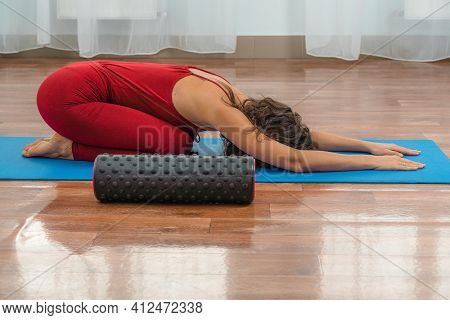 A Young Woman Works Out The Fascia Of The Muscles With A Massage Roller. On The Wooden Floor Against
