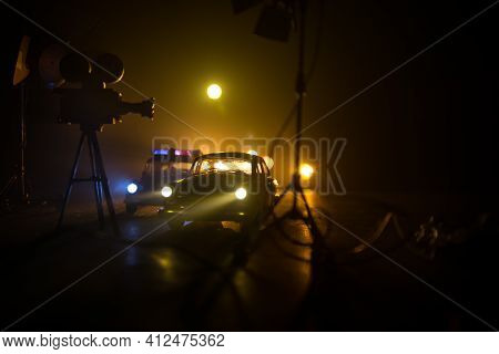 Action Movie Concept. Police Cars And Miniature Movie Set On Dark Toned Background With Fog. Police
