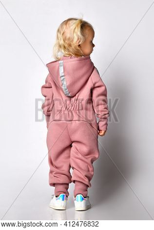 Back View A Little Cute Blonde Girl In A Pink Warm Comfortable Overalls With A Hood, Stands Against
