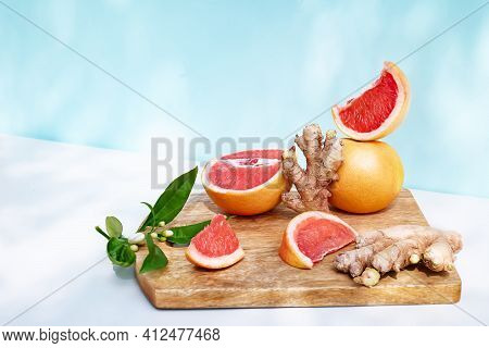 Fresh Healthy Grapefruit And Ginger On Sunlight With Shadows. Minimal Food Creative Concept On Blue