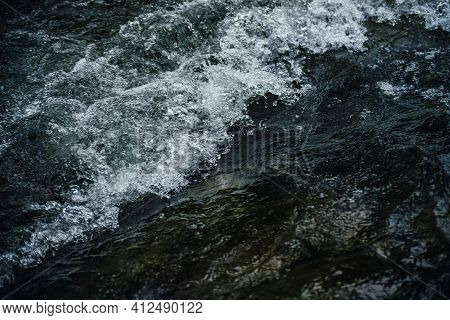 Nature Background Of Dark Water Stream Of Mountain River With Rapids. Full Frame Of Sea Surf. Natura