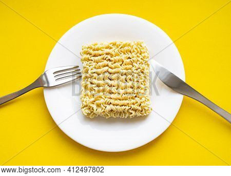 Noodles On A Plate. Vermicelli In The Shape Of A Square On A Round Plate. Fork And Knife And Noodles