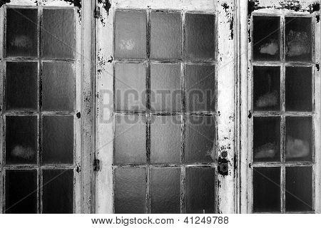 Old rusted metal doors with glass panes