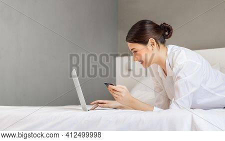 Young Woman Shopping Online With Credit Card And Laptop Computer On Bed. Women Doing Online Shopping