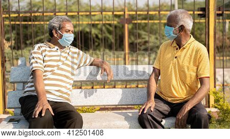 Two Old Senior Friends With Medical Mask Spending Good Time By Talking And While Maintaining Social
