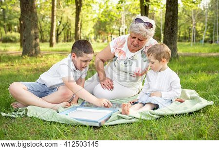 Young Boys And Grandmother Sitting In Sunny Summer Park. Little Kids And Grandmother. Grandma And Gr