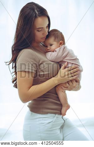 A Young Mother Is Holding Her Newborn Baby. Mother Of A Nursing Baby. Mother Breastfeeding Her Baby.