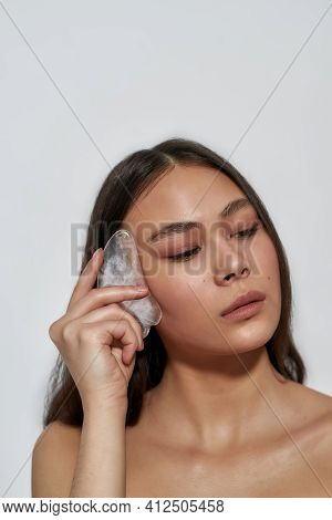 Asian Girl With Guasha Massager In Studio Doing Facial Massage. Clean Skin Care Concept. Brunette In