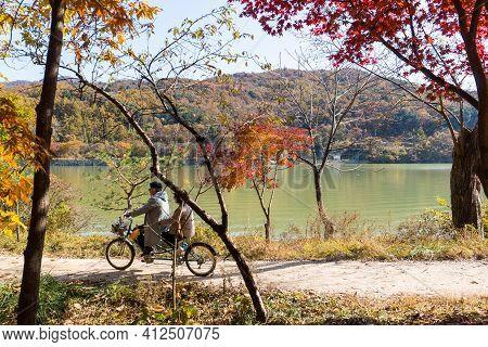 Gapyeong,south Korea-october 2020: Old Korean Asian Couple Riding Tandem Bicycle Alongt The Lake. Ko