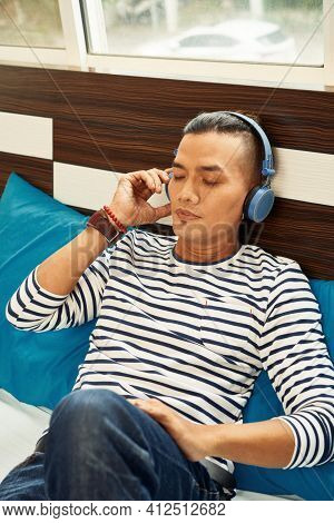 Young Vietnamese Man Resting On Bed In Dorm And Listening To Music In Headphones