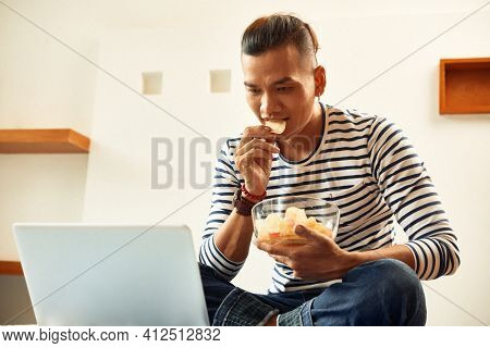 Young Vietnamese Man Eating Tasty Potato Chips And Watching Captivating Movie On Laptop Screen