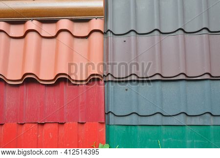 A Display Of Orange, Red, Gray, Brown And Green Metal Roof Tiles, Different Types Of Corrugated Meta