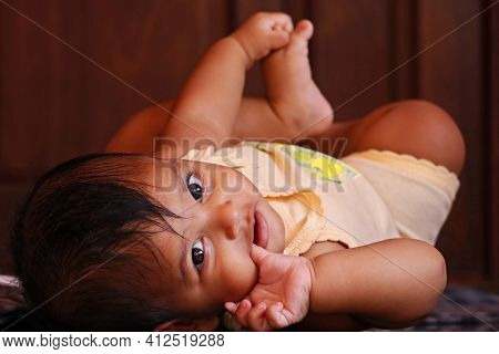 6 Months Cute Indian Baby Boy Lying On The Floor With Lovely Smile In Close Up