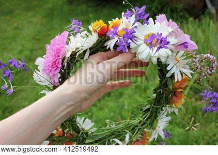 Midsummer Flower Wreath In Woman Hand On Green Grass Background. Scandinavian Summer Celebration. Gr