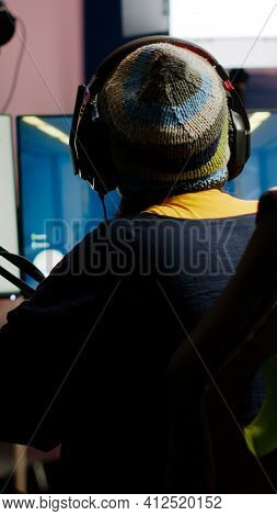 Back Shot Of Pro Gamer Woman Playing First Person Video Games Using Rgb Keyboard In Home Studio. Gam