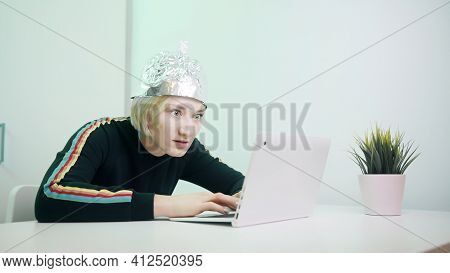 Crazy Woman Typing On Laptop With Foil Hat To Shields Her From 5g Waves, Internet, Electromagnetic F