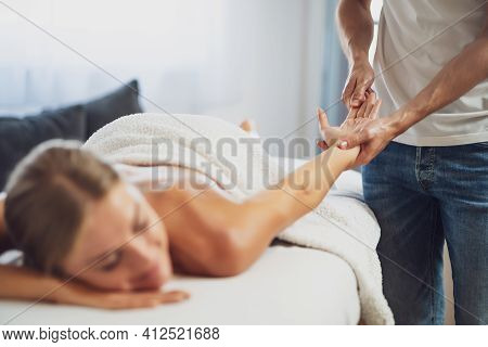 Professional Masseur Doing Therapeutic Massage. Woman Enjoying Massage In Her Home. Young Woman Gett