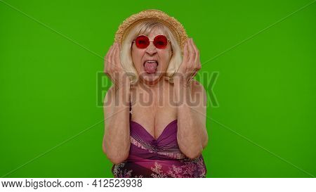 Funny Silly Senior Woman Tourist In Swimsuit, Fooling Around Making Stupid Brainless Expression