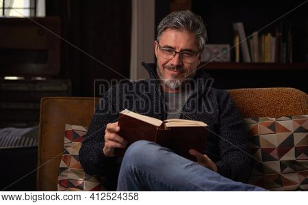 Happy man sitting on couch at home in cosy room reading book. Relaxing, leisure, education.  Portrait of mature age, middle age, mid adult man, bearded, glasses, smiling, authentic look.