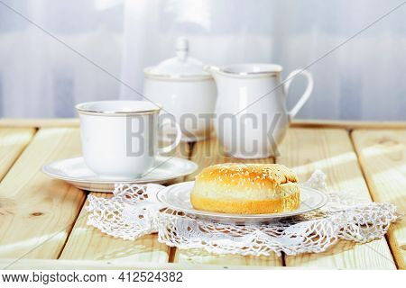 Fresh burger buns with sesame for breakfast at bright sunny morning. White porcelain cup, sugar bowl and creamer and lace doily on wooden table. Selective focus.
