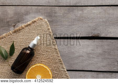 Orange Essential Oil In Glass Bottle With Green Leaf. Cosmetic Concept On Wooden Background On Sackc