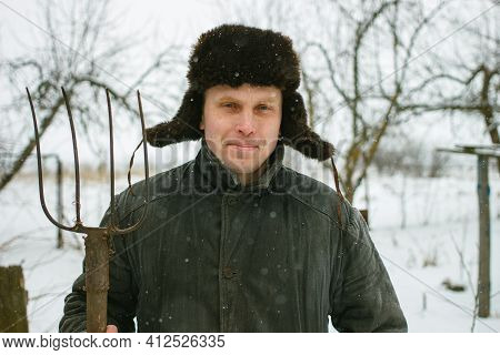 Peasant With Pitchfork In Winter Work In The Village