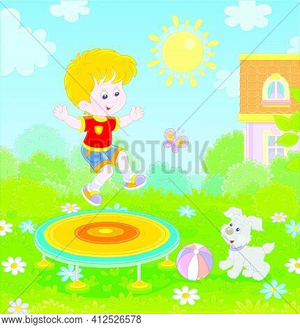 Happy Little Boy Playing With His Small Pup And Jumping On A Toy Trampoline On A Green Front Lawn On