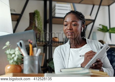 Young Black Business Lady With Clipoard In Hand Video Calling Her Coworker To Discussing Results Of