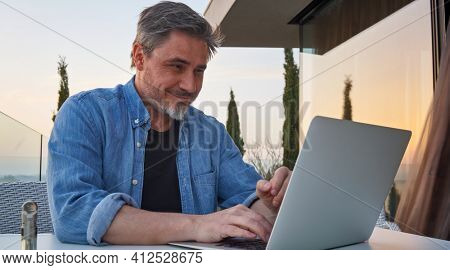 Happy man working online with laptop computer on terrace. Businessman in home office, browsing internet, tele working, video chat.