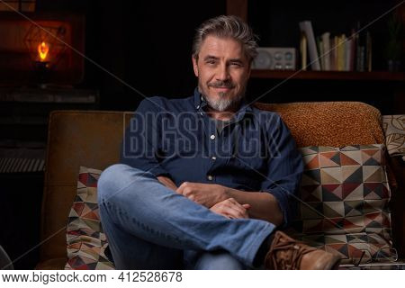 Portrait of older man at home in dark room sitting on couch. Happy smile, grey hair, bearded, . mature age, middle age, mid adult man in 50s.