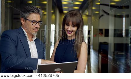 Happy business people working with tablet in office. Businessman and businesswoman teamworking.