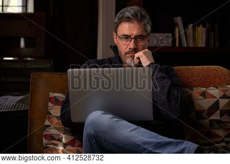Man sitting on couch at home with laptop computer. Businessman working in home office. Portrait of mature age, middle age, mid adult man, bearded, glasses, authentic look.