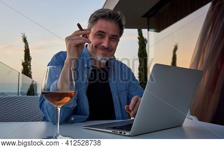 Man relaxing at home. Man sitting on balcony using laptop, enjoying wine and cigar. Home office, tele working, lifestyle, escape, freedom, getaway.