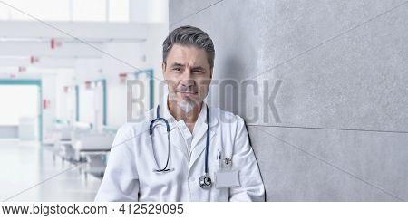 Medical portrait - Smiling doctor on hospital corridor, Trustworthy older man with gray hair.